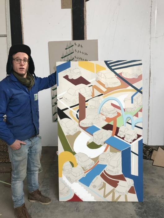 Victor Cord'homme présentant sa toile dans son atelier