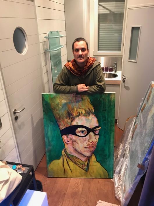 L'artiste Thibault Franc tenant une de ses peintures de la série Van GANG, variation sur le thème de Van Gogh revenant hanter Arles
